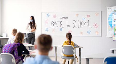 Enseignant avec masque facial accueillant les enfants à l'école après le verrouillage.