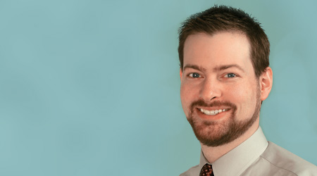 Bearded man smiles why wearing tie and collared shirt