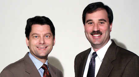 Picture of two men — one with a mustache — smiling for a picture