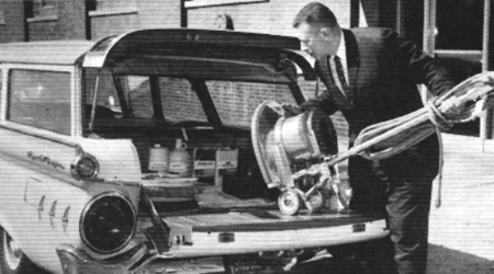 Man in black suit puts floor machine in station wagon in the 1950s