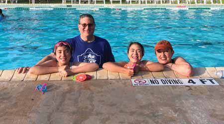 Two kids and two adults smile while swimming