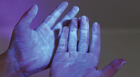 dirty contaminated hands under blacklight