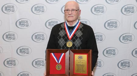 Man holds up awards he has won