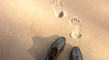 Work Life Balance Concept, Businessman take off his Working Oxford Shoes and leave it on the Sand Beach for Walk into the Sea on Sunny Day