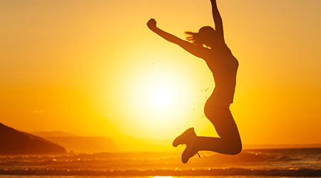 Silhouette of happy joyful woman jumping and having fun