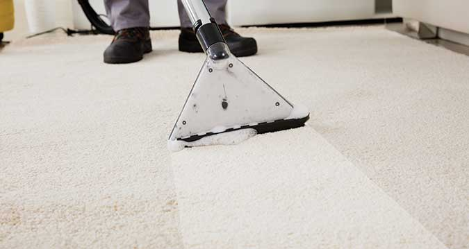Close up of a person cleaning carpet with a vacuum