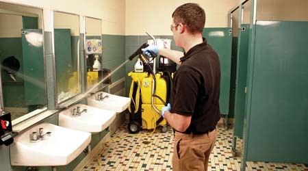 Man spray bathroom sink with spray-and-vac cleaning system