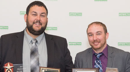 Two men pose for a picture while holding awards they were given