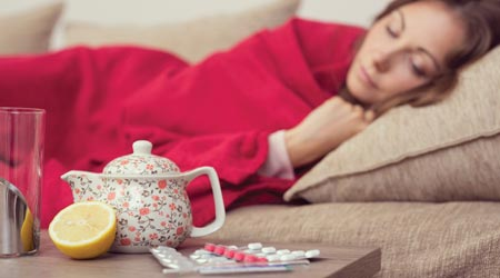 Woman with the flue lays under blanket with medicine and tea pot nearby
