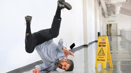 Man falls onto hard to the ground after slipping on wet floor