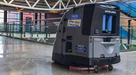 A robotic floor machine operates in an empty building