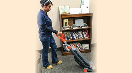 Female cleaner using a cordless upright