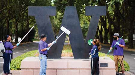 custodial workers at University of Washington cleaning campus sign