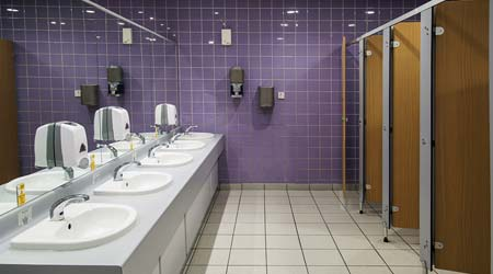 public restroom with clean sink, soap dispensers, paper towel, dryers and stalls