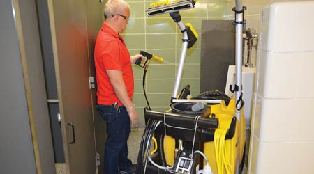 man at Aurora Public Schools using Kaivac machine to clean restroom