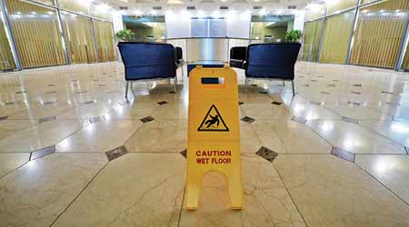 glossy tile floor in hotel lobby with wet floor sign