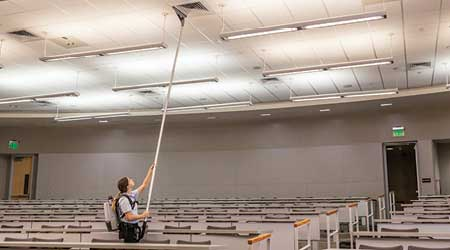 womany using battery backpack vacuum and extension wand to vacuum the dust from HVAC vent in univeristy classroom