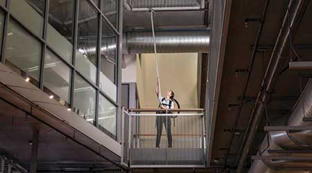 woman using a backpack vacuum and extension wands to reach elevated surfaces for vacuuming