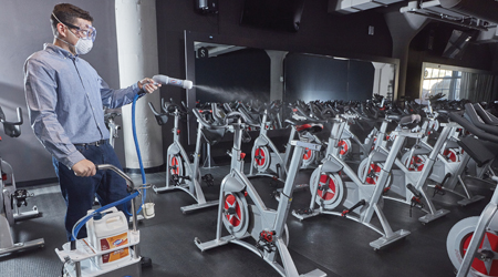 Man wearing mask cleans stationary bikes with electrostatic sprayer.