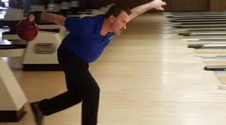 Middle-aged man throws bowling ball
