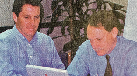 Two men use Macintosh laptop made in early 1990s