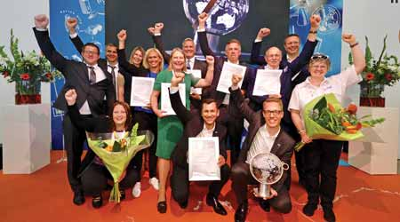 People smile with their fists up holding awards