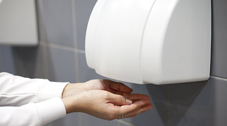Person cups hands under hand dryer