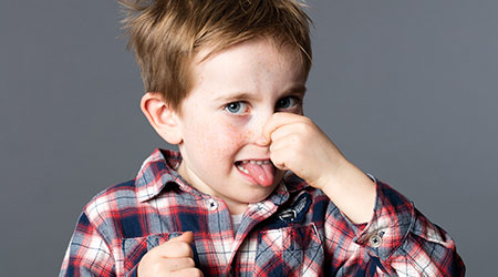 unhappy young boy pinching his nose for sign of bad odor, sticking out his tongue for humor and mischievous childhood