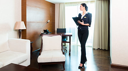 Housekeeping manager or assistant controlling or checking the room or suit of a hotel with a checklist on tidiness