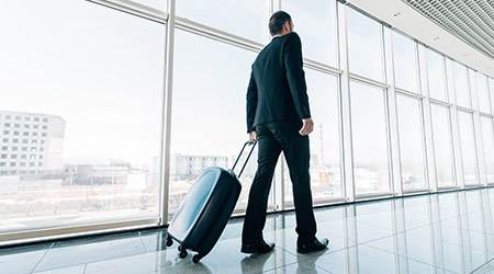 Man at the Airport with Suitcase walking to flight gate