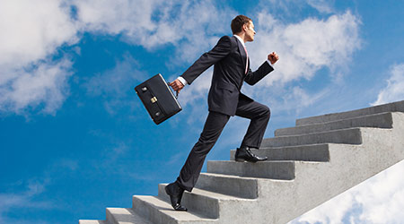 confident businessman with briefcase walking upstairs