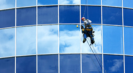 Male worker in overalls professional repair the windows in high-rise