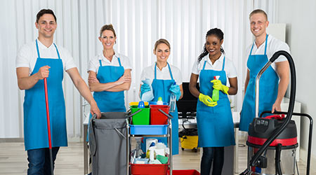Group Of Happy Cleaners Standing With Cleaning Equipments In Office