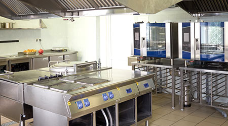 Kitchen room with stoves, sinks and refrigerators in restaurant