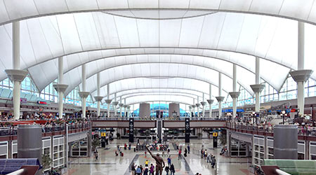 Passengers traverse through the Jeppesen Terminal, (also known as the Great Hall) at Denver International Airport, DEN, a large hub airport in the central United States.
