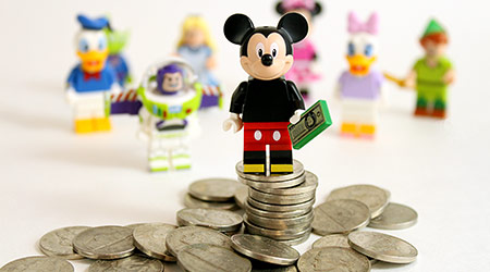 Studio shot of LEGO minifigure Mickey Mouse on top of a pile of money with other Disney characters in the background