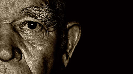 Elderly man's face over black background