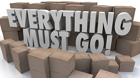 Everything Must Go words in 3d letters surrounded by cardboard boxes in a store warehouse