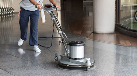 Woman worker cleaning the floor with polishing machine