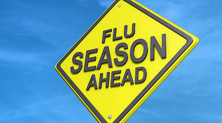 A yield road sign with Flu Season Ahead