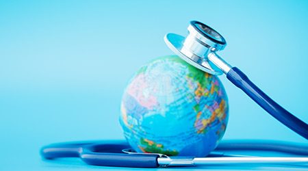 Save the wold and Global healthcare concept. Stethoscope wrapped around globe on blue background