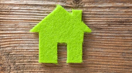 Green small house on wooden background