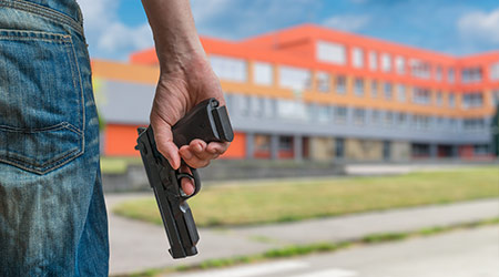 Gun control concept. Young armed man holds pistol in hand in public place near high school