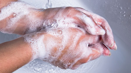 Woman washing soapy hands in sink