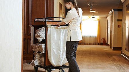 housekeeper at hotel with linen cart
