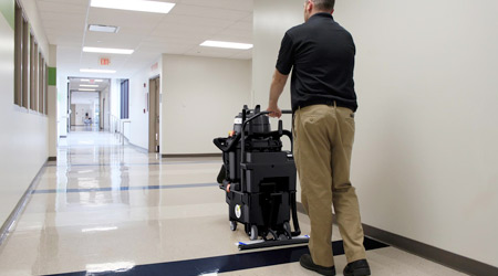 Man pushing a floor machine down an empty school hallway