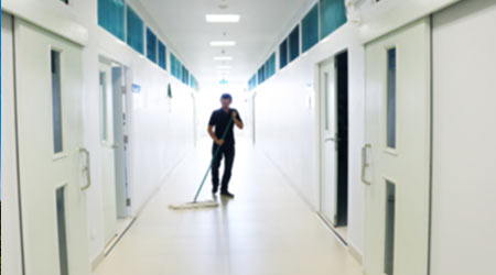 blurred image of Asian janitor man mopping floor in walkway after school