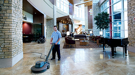 man scrubbing lobby floor with equipment