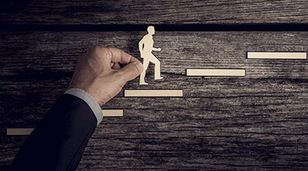 Retro style image of a successful businessman climbing the corporate ladder using paper cutouts