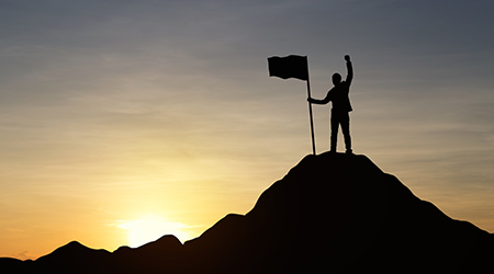 Silhouette of businessman holding a flag on top mountain, sky and sun light background